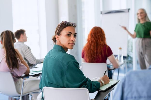 카메라를 보고 실내 교실에 앉아 젊은 대학생의 초상화.