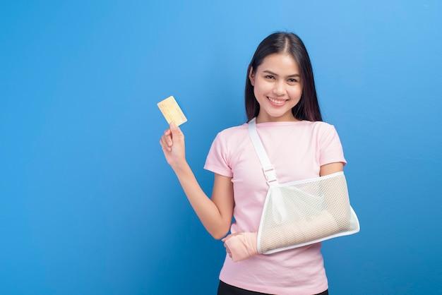 스튜디오, 보험 및 건강 관리 개념에서 파란색 배경 위에 신용 카드 또는 의료 보험 카드를 들고 슬링에 다친 팔을 가진 젊은 여자의 초상화