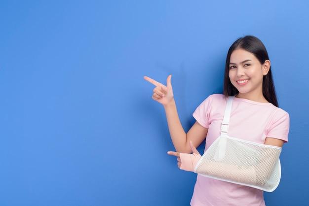 Портрет молодой женщины с травмированной рукой в перевязке через синюю стену
