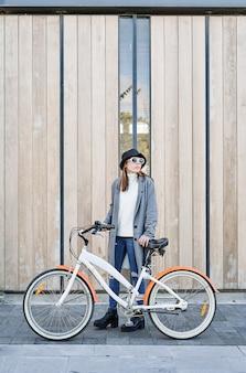 灰色のジャケット、白いセーター、街で自転車に乗る帽子を着た肖像画の若いかわいい白人の女の子