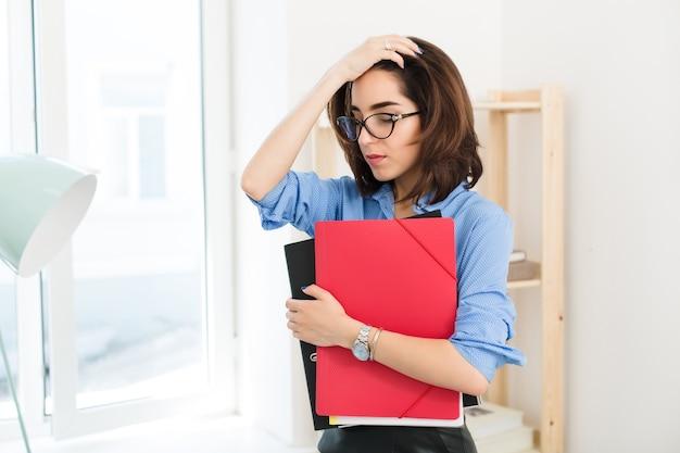 Портрет брюнетки в голубой рубашке, стоящей в офисе. она держит папки и выглядит разочарованной.