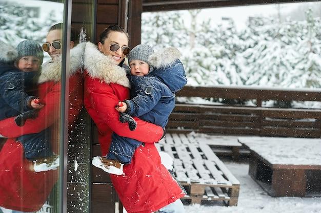 雪に覆われたクリスマスツリーを背景に、家の近くで冬に子供を腕に抱えた赤いジャケットを着た美しい若い母親の肖像画。