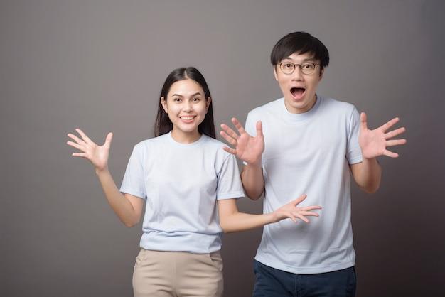 青いシャツを着て幸せなカップルのportriatはグレーの上で楽しんでいます