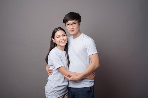 青いシャツを着て幸せなカップルの肖像画が灰色でお互いを抱いています。