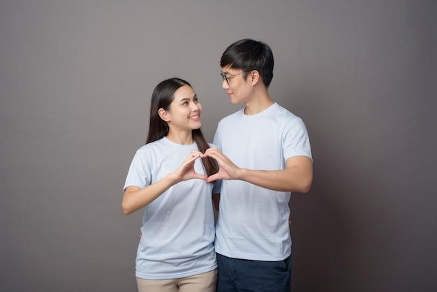 파란색 셔츠를 입고 행복한 커플의 portriat는 회색에 손으로 하트 모양을하고있다