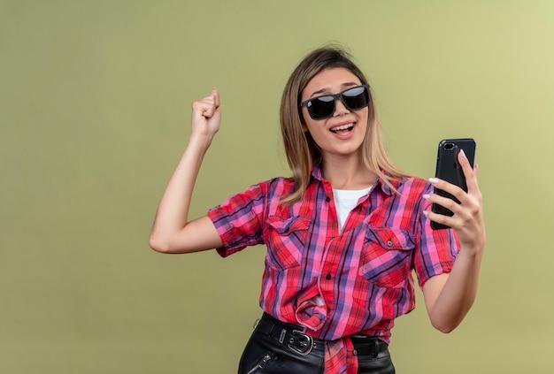 緑の壁にくいしばられた握りこぶしを上げている間サングラスで携帯電話でselfieを取るチェックシャツを着たポジティブな素敵な若い女性