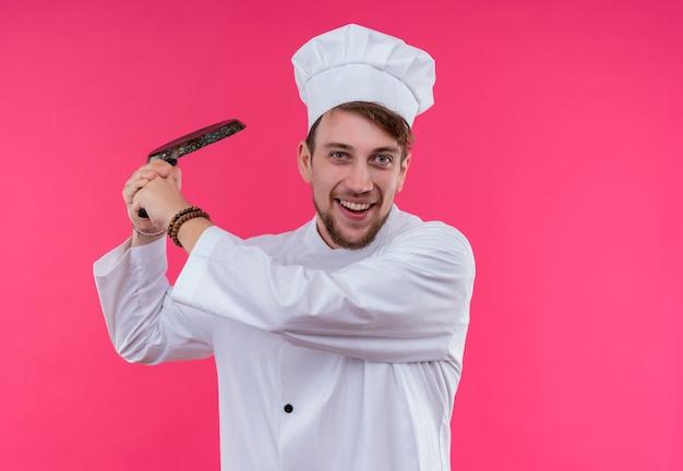 ピンクの壁を見ながら野球のバットのようにフライパンを保持している白い制服を着たポジティブな若いひげを生やしたシェフの男