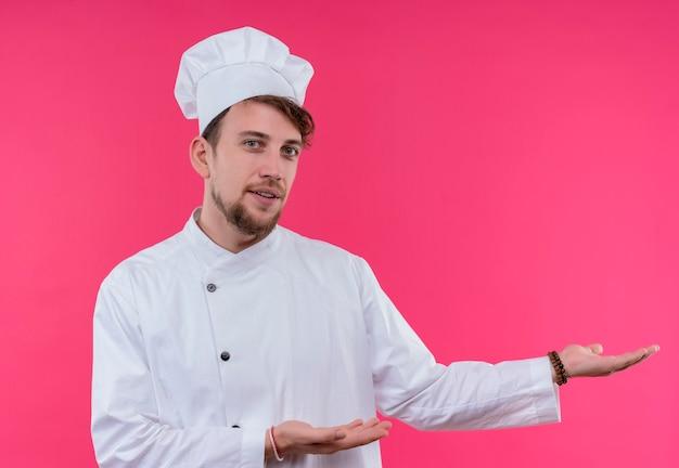 Позитивный молодой бородатый шеф-повар в белой форме представляет и приглашает подойти, глядя на розовую стену
