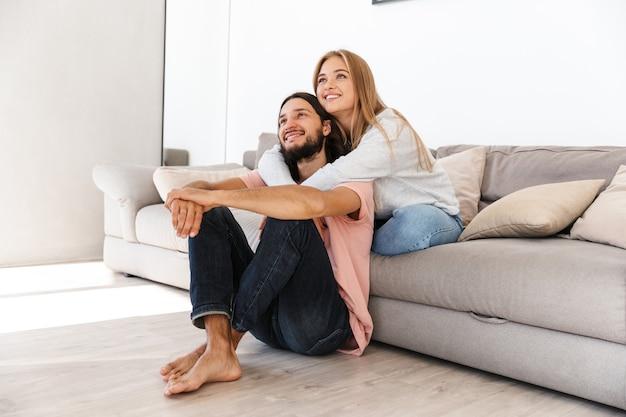 ソファで前向きな若い愛情のあるカップルは、脇を見て家で屋内でテレビ映画を見ます。