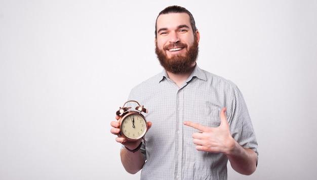 ポジティブな若い男がカメラに微笑んでいて、時計を持って白い壁の近くでそれを指しています