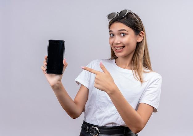 흰 벽을 보면서 휴대 전화의 빈 공간을 보여주는 동안 웃 고 선글라스에 흰색 티셔츠에 긍정적 인 젊은 여자