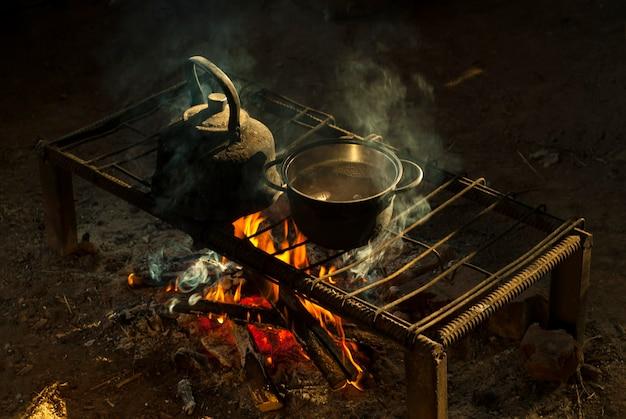 유목민 주택의 금속 막대로 만든 이동식 난로 위의 불 위에 냄비와 주전자가 놓여 있습니다.