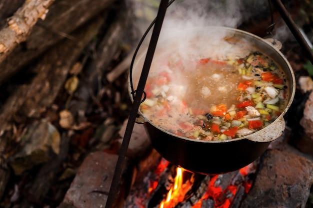 Кастрюля с горячей едой в лесу отдых на природе ночью