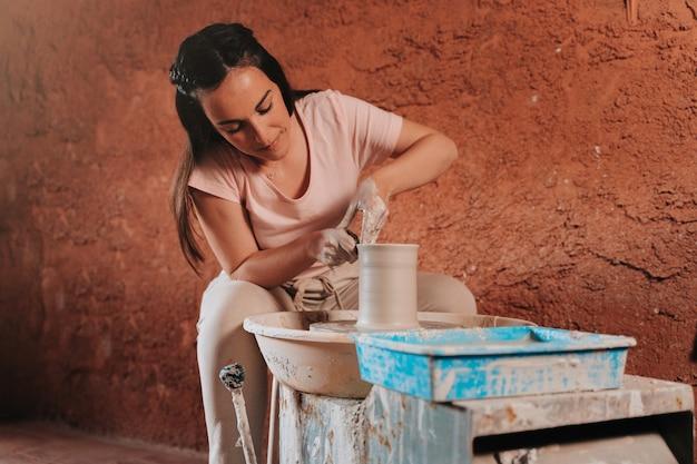 도공 여성이 작업장에서 테라코타라는 재료로 만들고있는 꽃병을 만들고 있습니다.