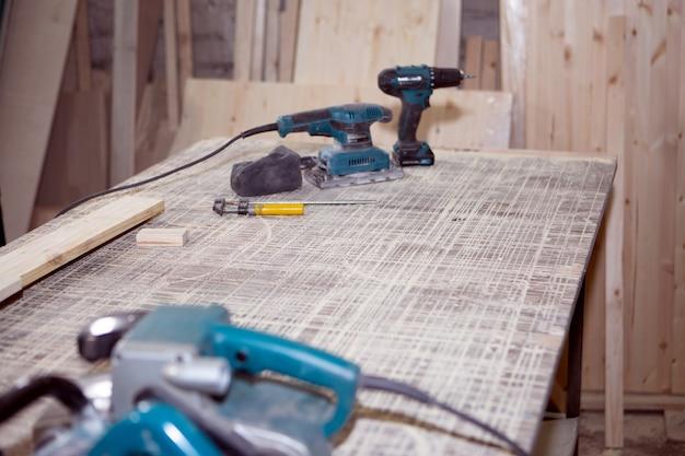 Электроинструмент для обработки дерева пыльно лежит на рабочем столе в конце рабочего дня