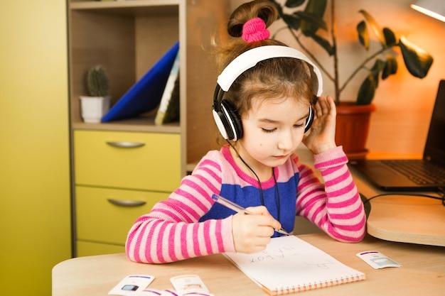헤드폰을 가진 유치원 소녀는 노트북에 쓰는 교육 프로그램을 공부하는 테이블에서 집에서 참여하고 있습니다.