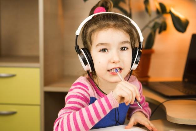 헤드폰이있는 유치원 소녀가 교육 프로그램을 공부하는 테이블에서 집에서 참여하고 있습니다.