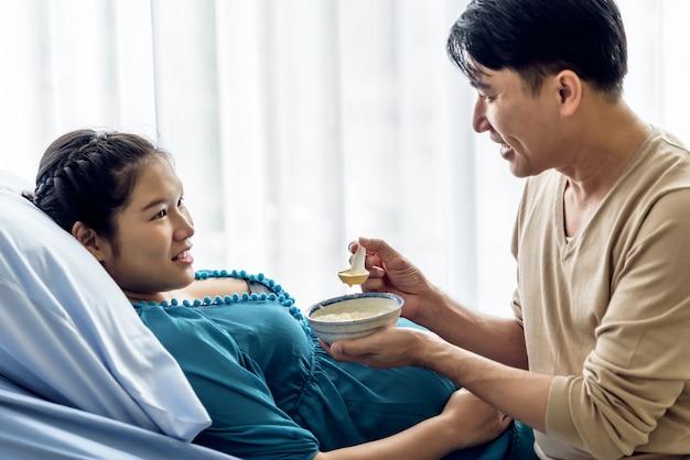 Беременная азиатка лежит в постели пациента, а ее муж заботится о кормлении мягкой пищей