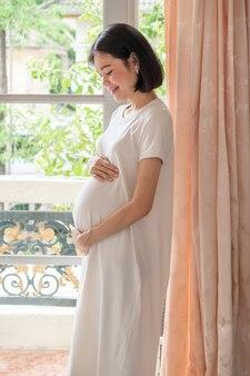 평상복을 입은 한 임신한 아시아 여성이 서서 기분 좋은 표정으로 배꼽을 바라보고 있습니다.