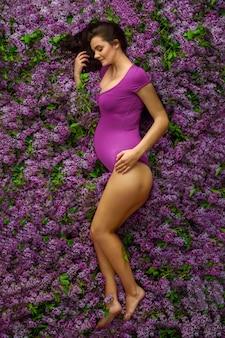妊娠中の美しい女性が紫色のボディスーツを着て彼女の側に横たわっています。ライラックは彼女のいたるところに散らばっている。