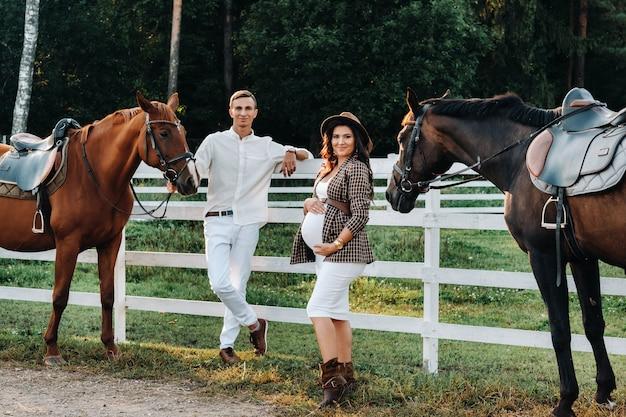 白いフェンスの近くの馬の横に帽子をかぶった妊婦と白い服を着た男が立っています。馬を持った男とスタイリッシュな妊婦。夫婦。