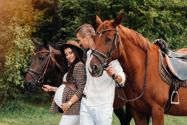 모자를 쓰고있는 임신 한 여자와 흰 옷을 입은 남편은 자연 속에서 숲속의 말 옆에 서 있습니다.
