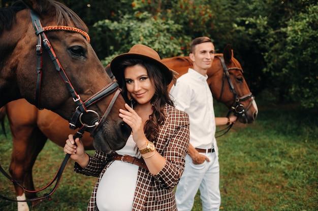 自然の森の馬の横に帽子をかぶった妊婦と白い服を着た夫が立っています。馬を持った男性とスタイリッシュな妊婦。家族。