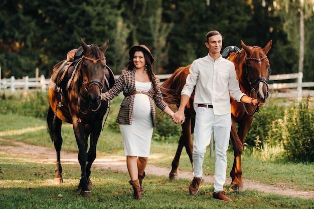 모자를 쓴 임신 한 소녀와 흰 옷을 입은 남편은 자연 속에서 숲속의 말 옆에 서 있습니다.