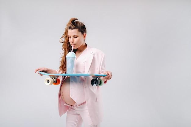 彼女の手にスケートボードを持つピンクのスーツを着た妊婦は、灰色の背景にジュースを飲みます。