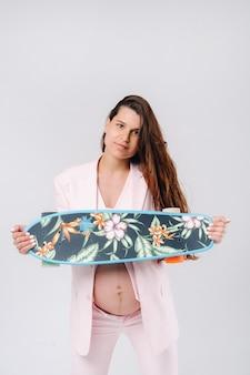 スケートボードを手にピンクのスーツを着た妊婦が灰色の背景に立っています。