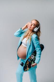手にスケートボードとヘッドフォンを持ったターコイズブルーのスーツを着た妊婦が灰色の背景に立っています Premium写真