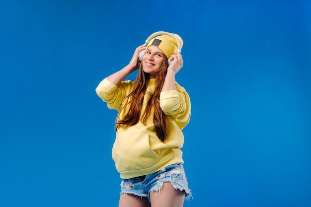 黄色のジャケットとヘッドフォンで妊娠中の女の子が青い背景に立っています。