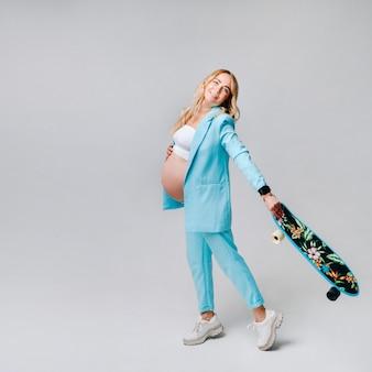 회색 배경에 손에 스케이트보드를 들고 청록색 옷을 입은 임신한 소녀.