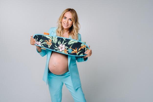 灰色の背景に彼女の手でスケートボードとターコイズブルーの服を着た妊婦。