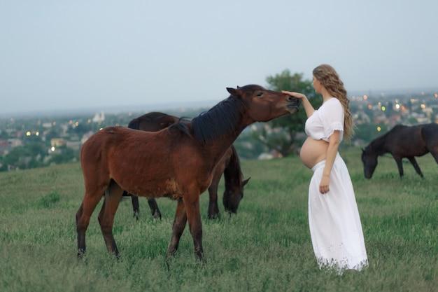 白い妊娠中の女の子は、緑の牧草地で馬と通信します。妊娠中の女性のための治療とリラクゼーション。