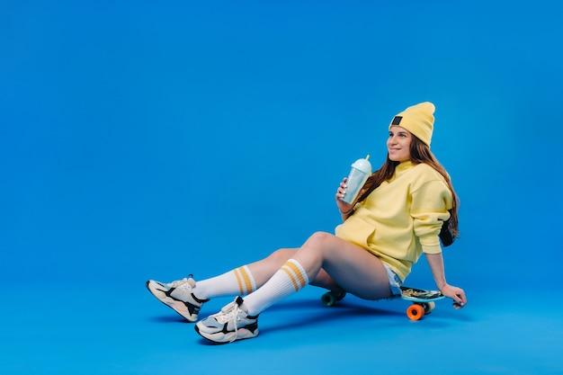 ジュースのガラスと黄色の服を着た妊婦は、青い背景の上のスケートボードに座っています。
