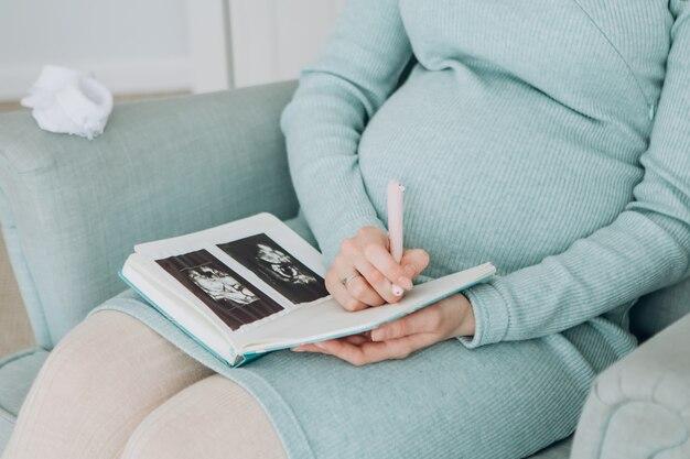 Беременная девушка держит снимок узи, беременная женщина в синем платье сидит в кресле