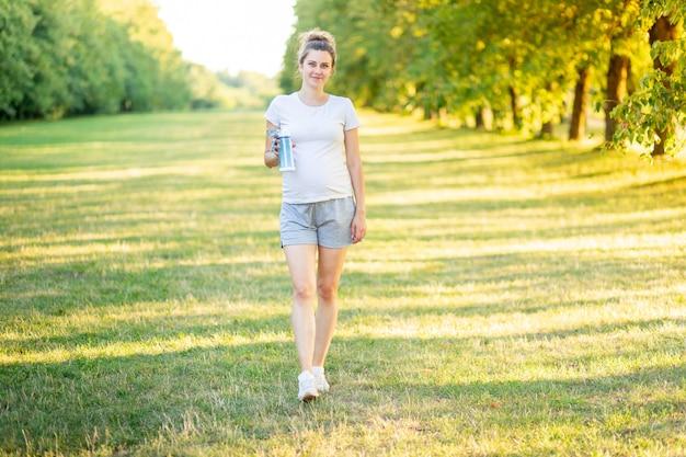 Беременная девушка летом занимается спортом на природе и пьет воду из бутылки