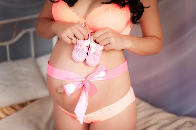 Беременная девушка с бантом на животе держит детские носки.