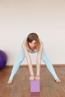 妊娠中の健康な女性が明るいスタジオでトレーニングします。健康的な生活様式