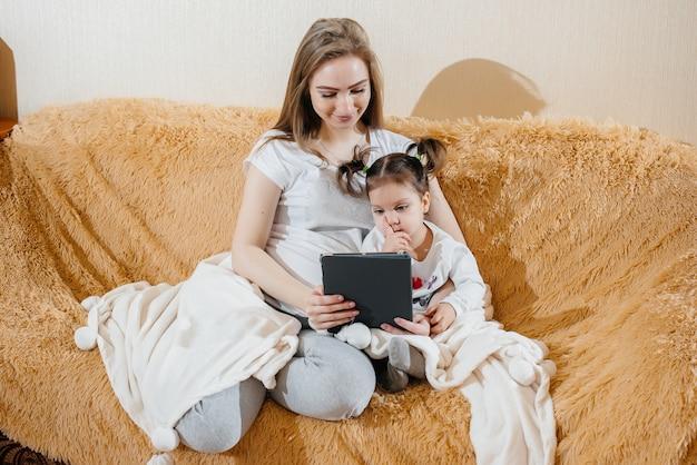 妊娠中の母親が小さな娘と一緒にソファに座って、ガジェットで遊んでいます。