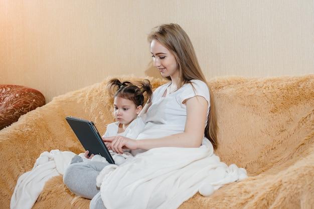 임신 한 어머니는 작은 딸과 함께 소파에 앉아 가제트를 가지고 놀고 있습니다.