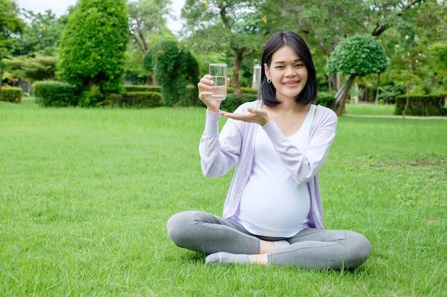 Беременная мать сидит со стаканом чистой питьевой воды для хорошего здоровья.