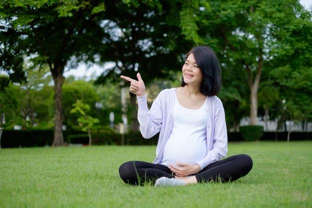 カジュアルな服を着た妊娠中の母親が笑顔でフィールドに座って、ポーズで指を指しています。