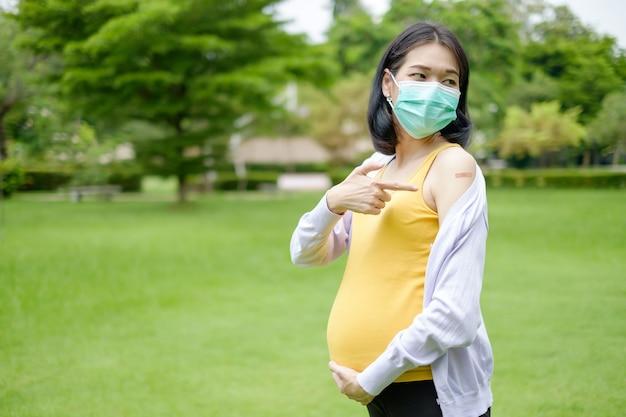 紫と黄色のカジュアルな服を着ている妊娠中の母親は、予防接種を受けた後、上腕に指先の絆創膏を示しています。