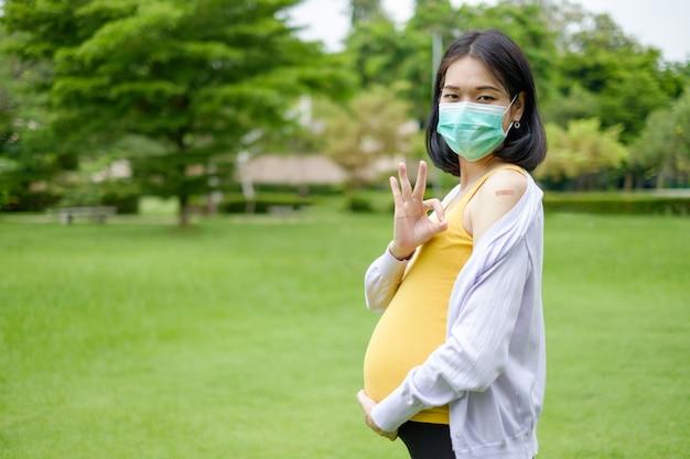 紫と黄色のカジュアルな服を着ている妊娠中の母親は、予防接種を受けた後、上腕に石膏を示しています。