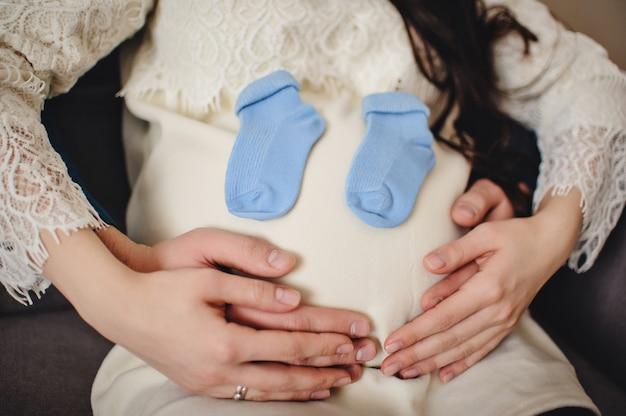 Беременная жена, мужчина держит носки руками вокруг круглого живота. вид на живот беременной жены. ждет ребенка. счастливый портрет, концепция семейного праздника. закройте вверх.