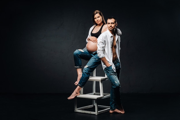 임신 한 여자와 검은 배경에 스튜디오에서 흰 셔츠와 청바지에 남자.