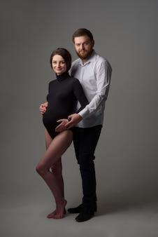 妊娠中の女性と彼女の夫は灰色の背景に抱いています。赤ちゃんを期待しているカップル。