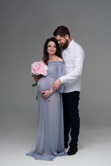 Беременная женщина и ее муж обнимаются на серой стене